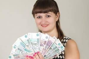 12 Month Payday Loans girl holding cash in front of face