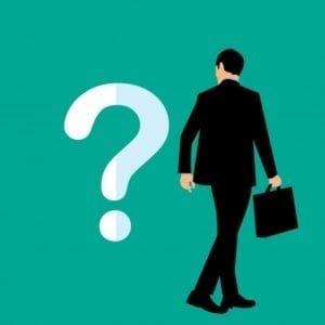 frequently asked loan questions man in suit looking at question mark