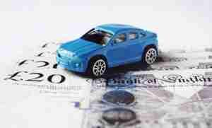 bad credit car finance blue car sitting on cash notes