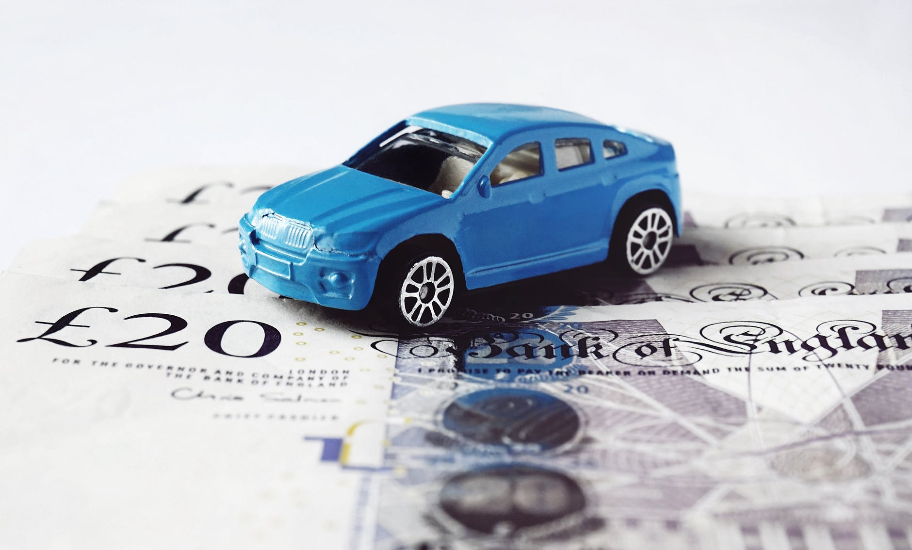 bad credit car finance blue car sitting on cash notes