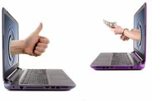 Borrow Money Online Same Day hands hold money from laptop screens