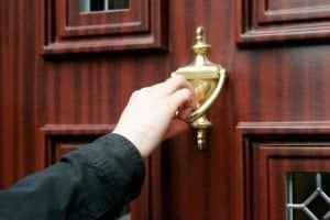 Agent Loans To Your Door knocking on front door knocker