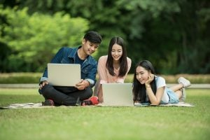 Student Finance Student Loans using laptops on lawn