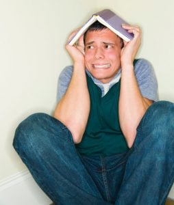 man hiding under open book on head