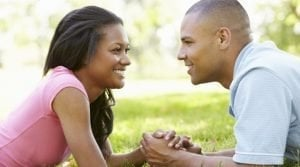loan in joint names romantic couple in park holding hands on grass