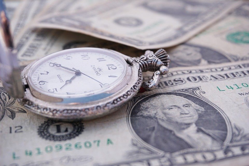 money loans fast pocket watch on top of cash notes