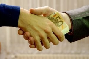 most accepted loan company handshake with cash notes in between