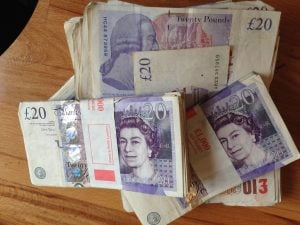 borrow 5000 pounds sterling cash notes on table in bank bundles